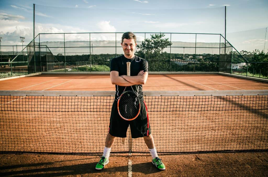A guy standing on a tennis court with a racket and tennis shoes